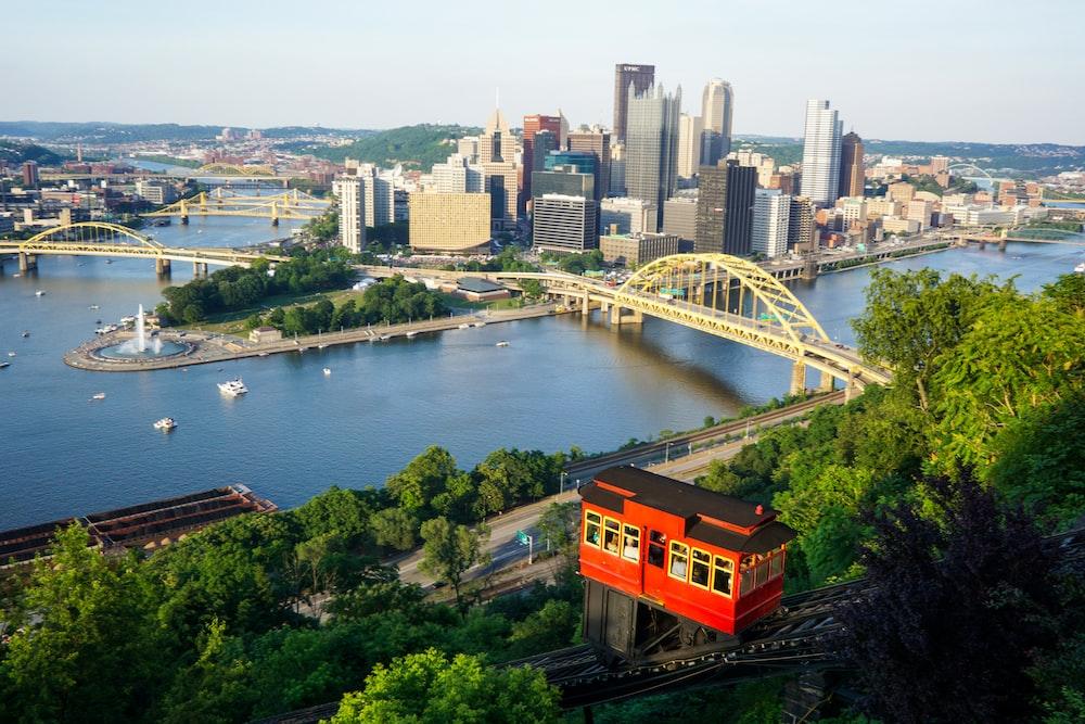 orange train on bridge over river during daytime