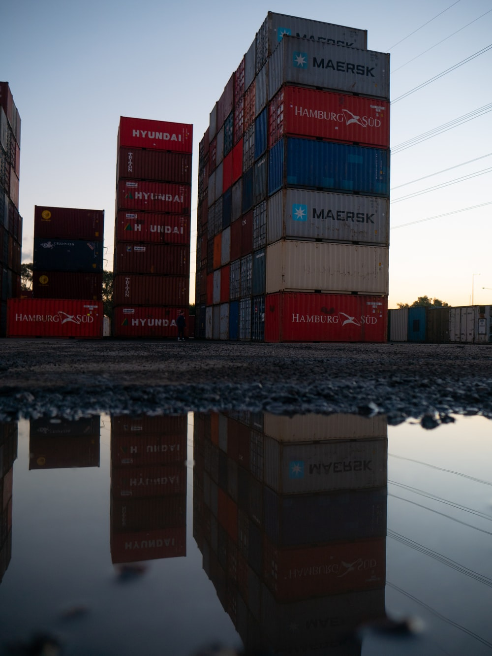 red and blue cargo containers on brown wooden dock during daytime