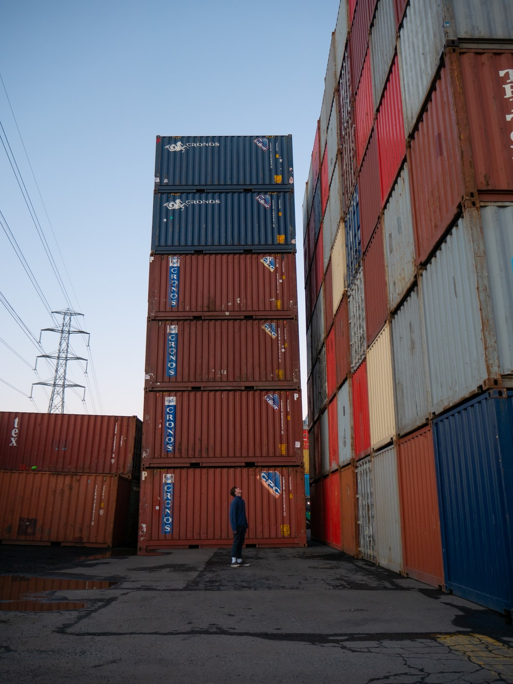 man in blue shirt walking near red cargo containers during daytime