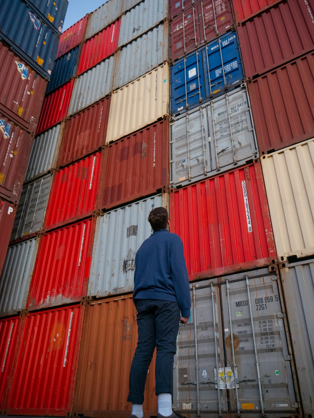 man in blue long sleeve shirt standing in front of red and blue intermodal containers