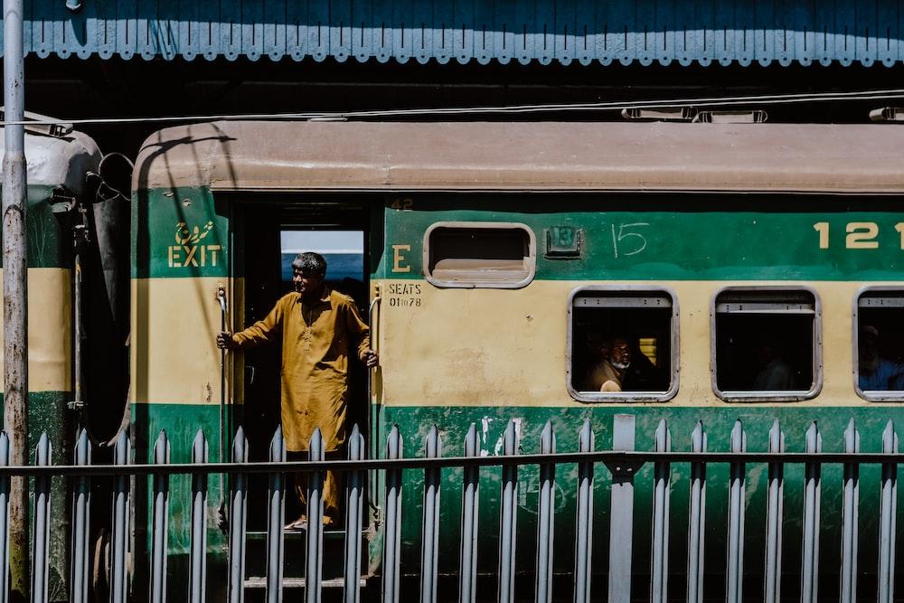 woman in brown coat standing beside green train