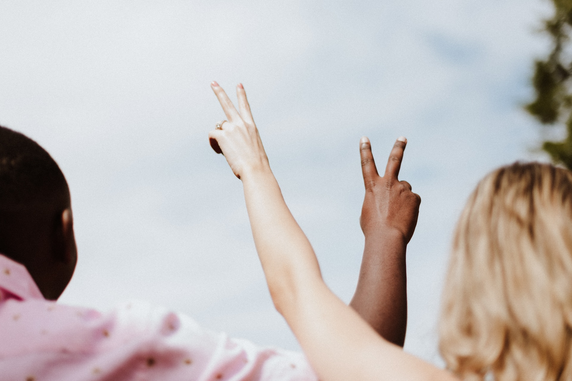 woman in white and pink floral shirt raising her hands