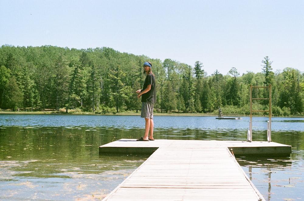 woman in black shirt standing on dock near lake during daytime