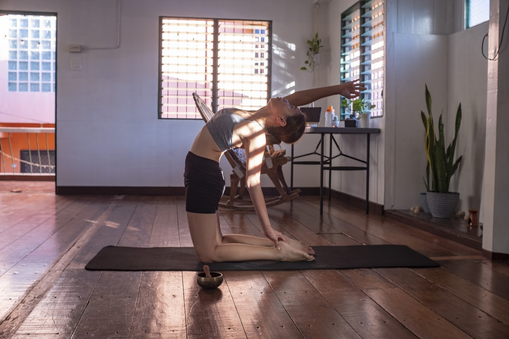 woman in black shorts and white tank top doing yoga