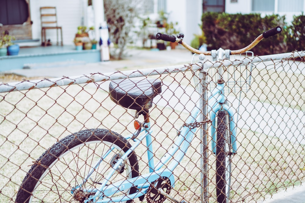 blue and black bicycle leaning on blue metal fence during daytime