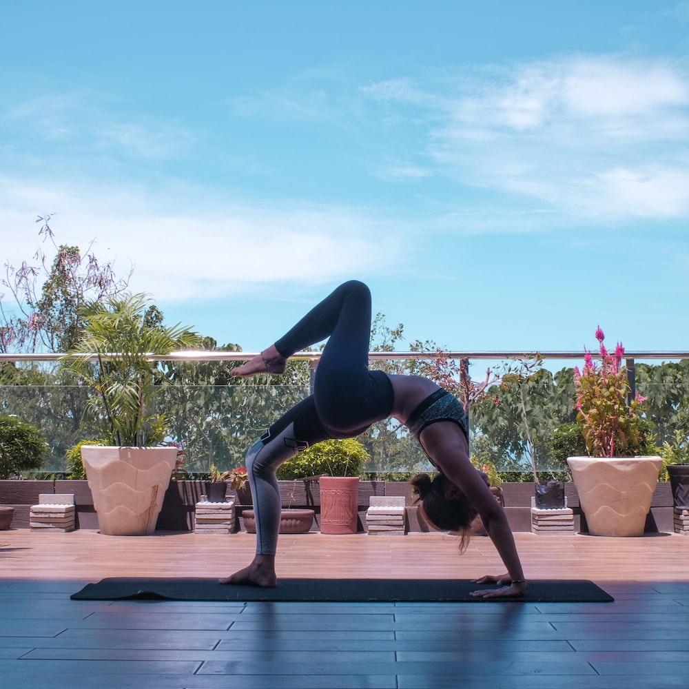 woman in black leggings and black tank top doing yoga