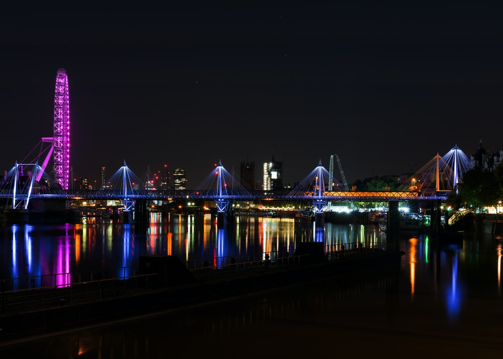 lighted bridge over water during night time