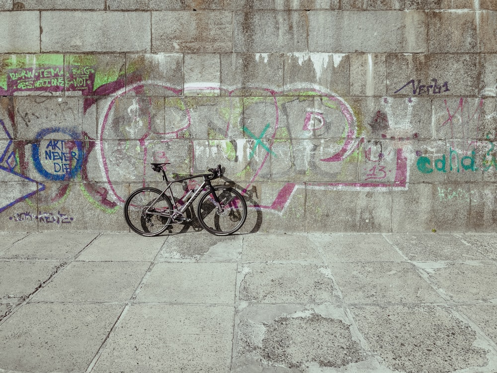 black bicycle parked beside wall with graffiti