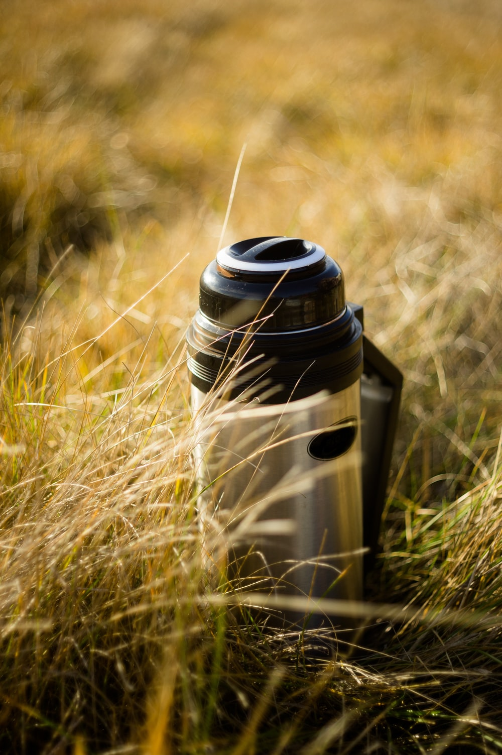 white and black vacuum flask on green grass