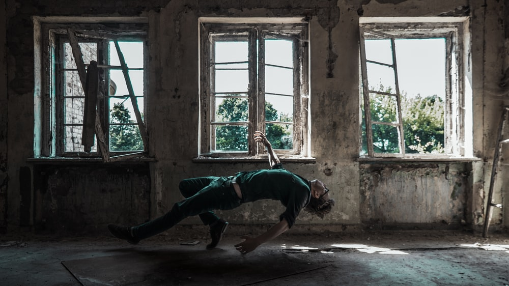 man in green t-shirt and black pants lying on concrete floor