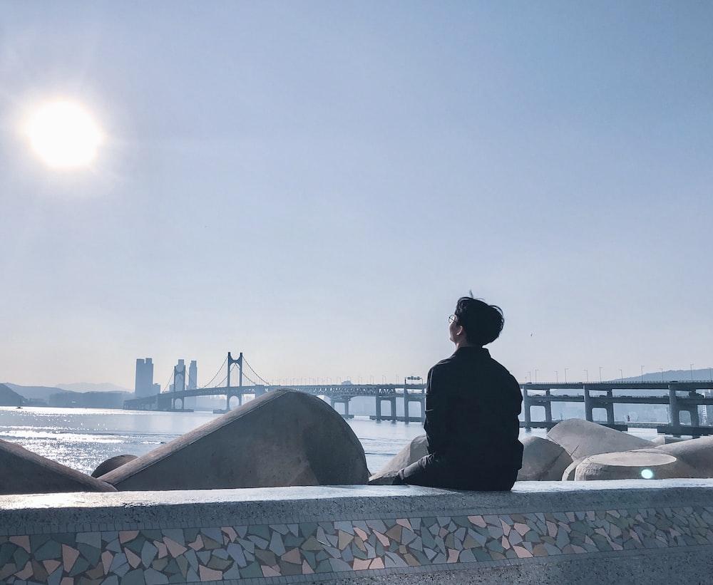 man in black jacket sitting on white bench