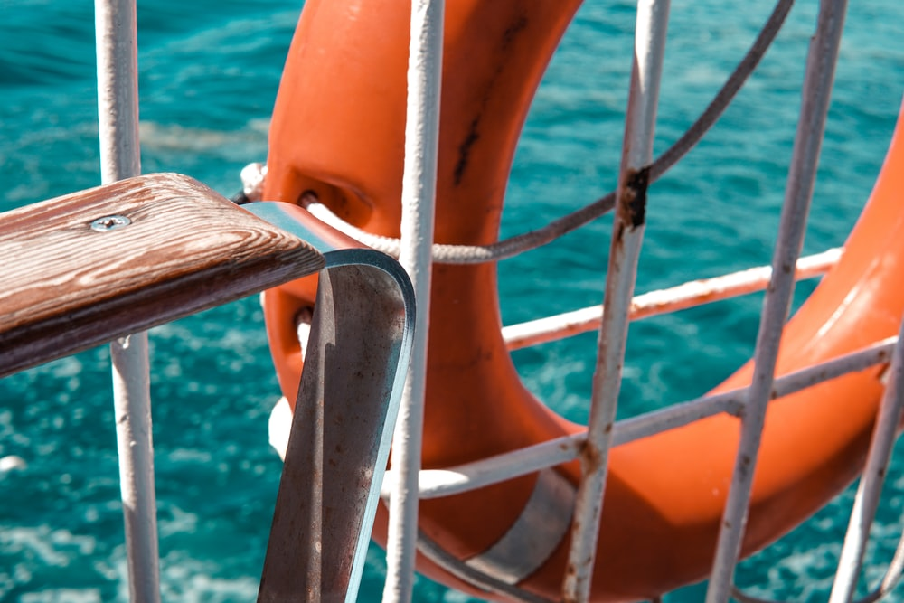 orange and white inflatable ring on blue sea during daytime