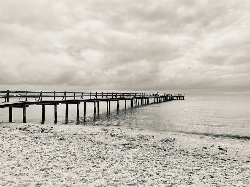 gray wooden dock on sea under gray clouds