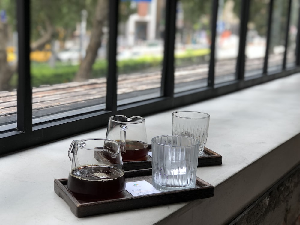 clear drinking glass on brown tray