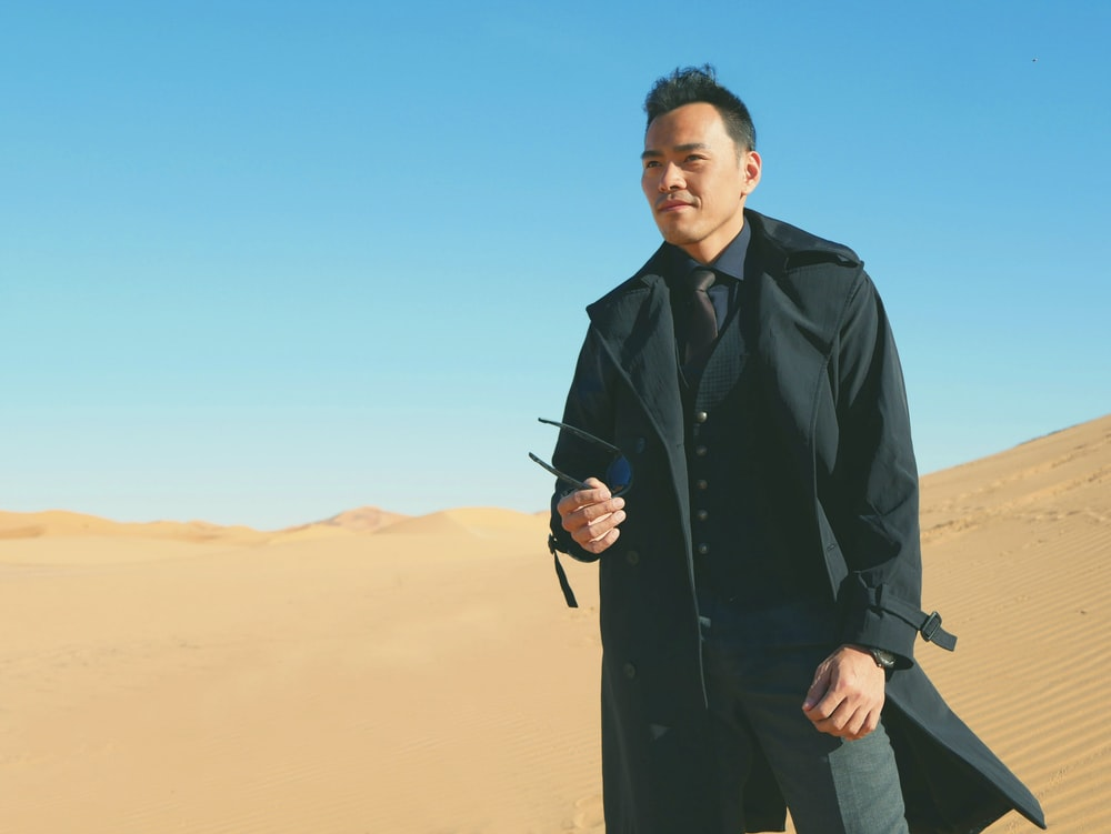 man in black suit standing on desert during daytime