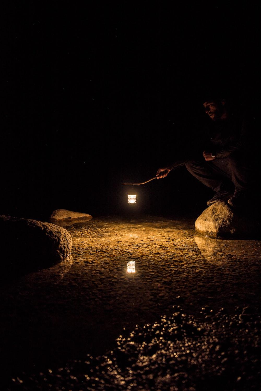 man in black shirt sitting on rock during night time
