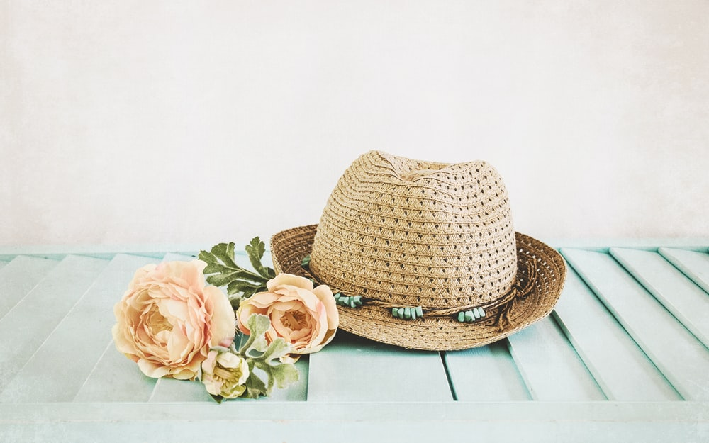 brown straw hat on white wooden table
