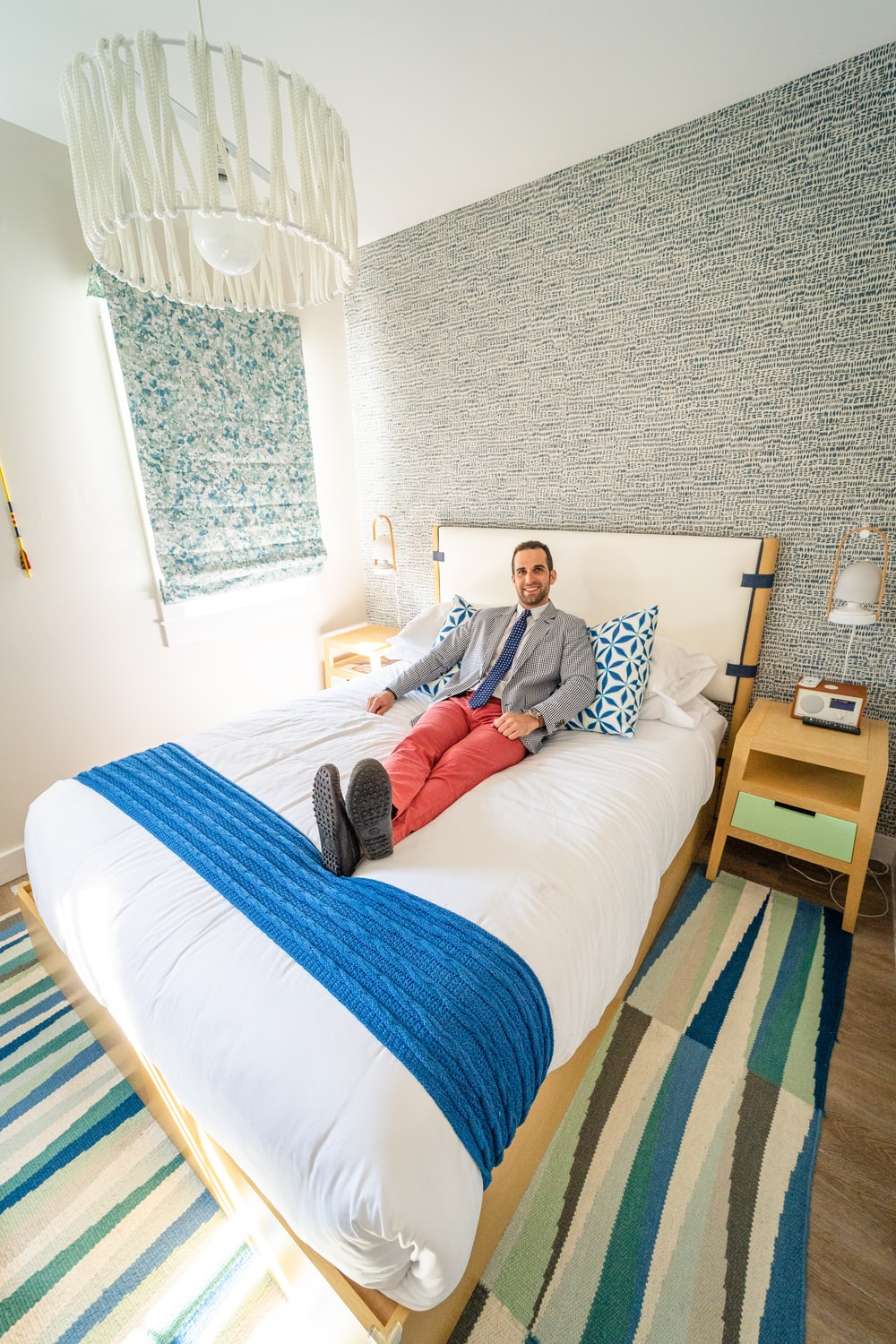 man in white and blue stripe dress shirt sitting on white bed