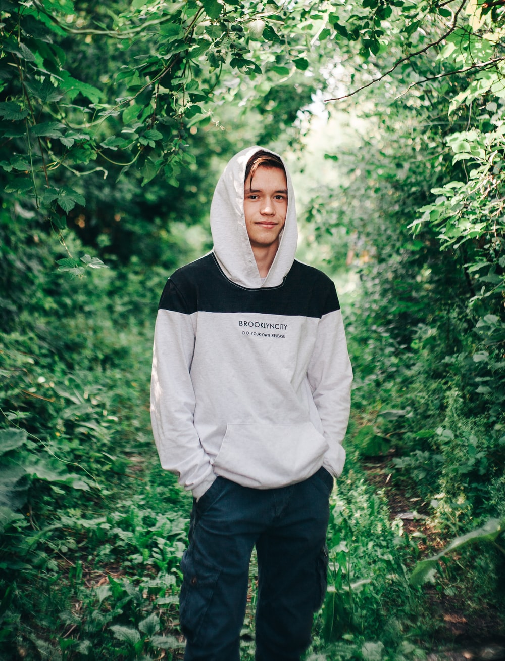 man in gray hoodie standing in forest during daytime