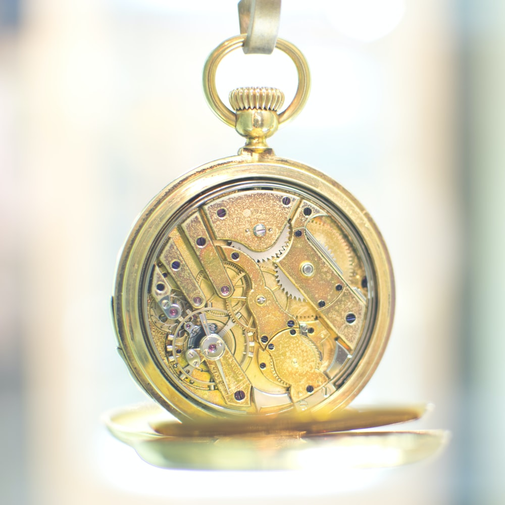 gold pocket watch on white surface
