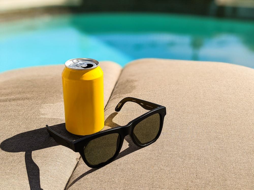 black framed eyeglasses beside yellow can