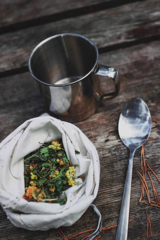 stainless steel spoon beside vegetable salad in stainless steel cup