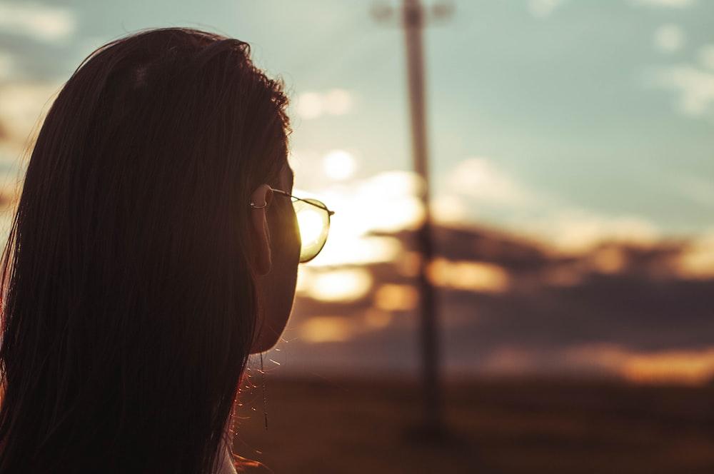 woman wearing black framed eyeglasses during sunset