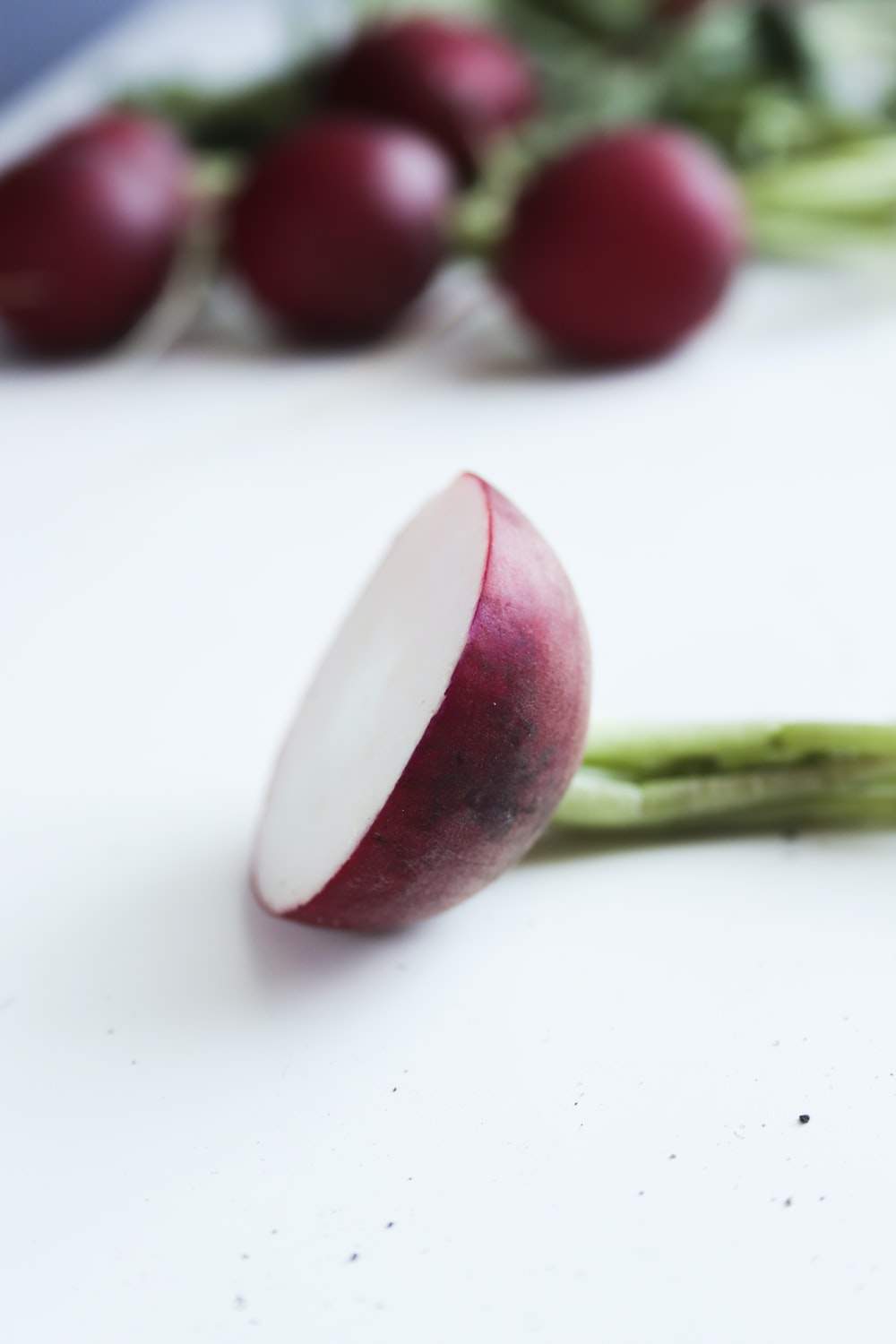 red and white fruit on white surface