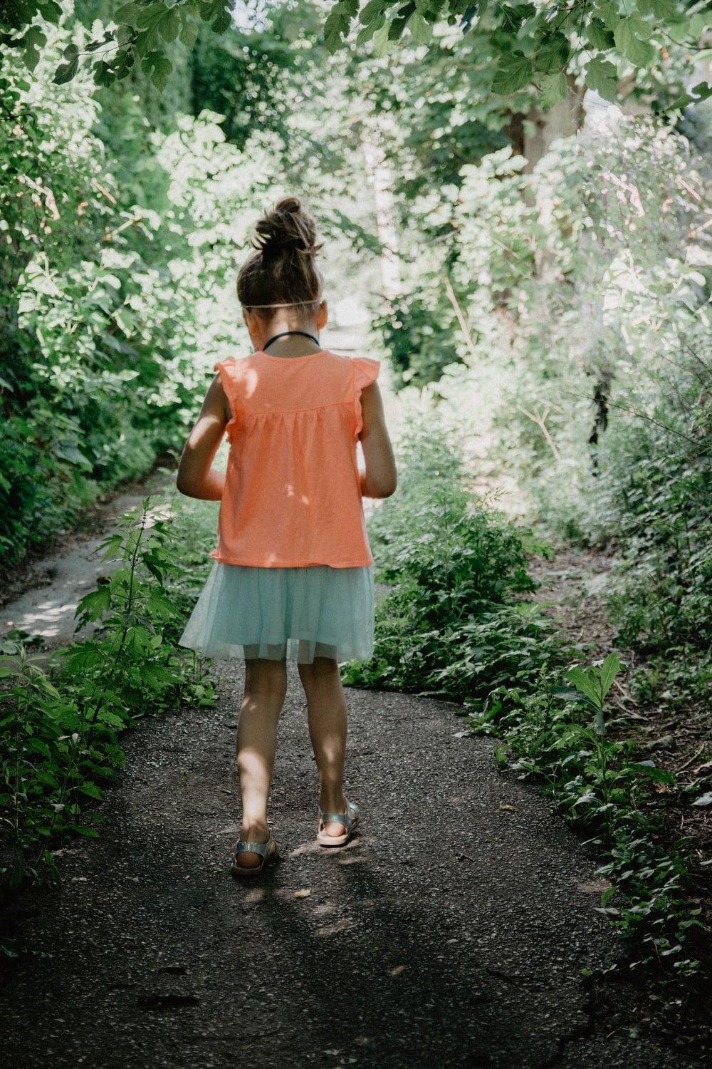 woman in pink tank top and blue denim shorts standing on pathway between green plants during