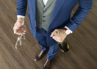 man in blue suit jacket holding clear glass mug