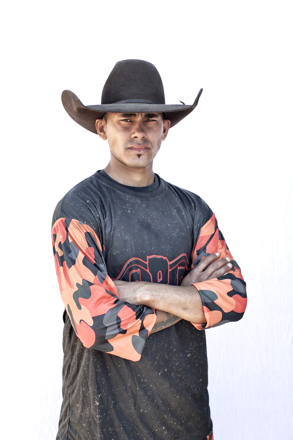 man in black cowboy hat and black red and blue crew neck long sleeve shirt