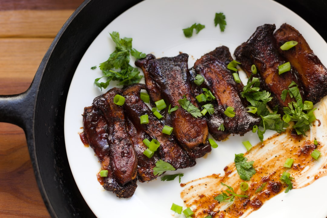 "Vegan Mushroom BBQ ""RIbs"" garnished with green onions, bbq sauce, and cilantro."