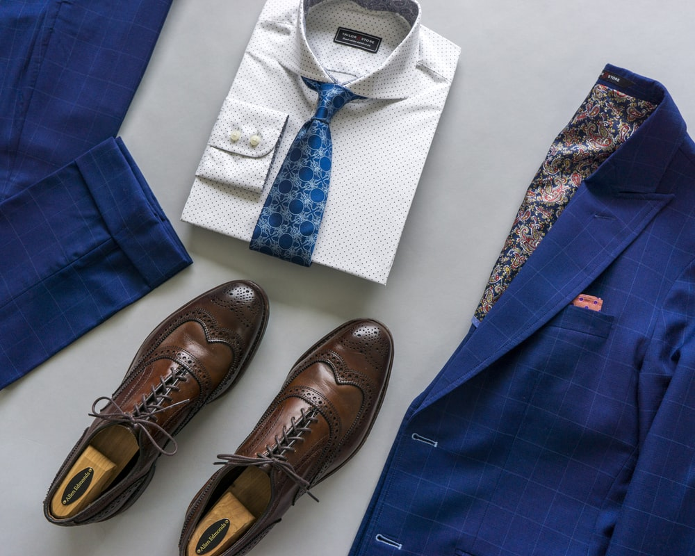blue and white necktie beside brown leather shoes