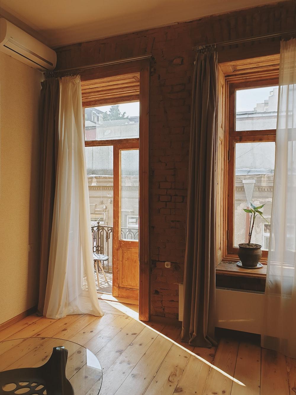 white window curtain near brown wooden door