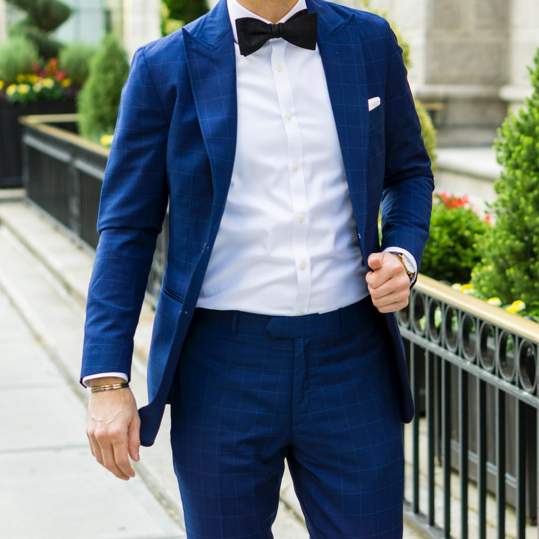 Dapper Professional walking outside wearing a custom blue plaid suit, a white dress shirt and a black bow tie.