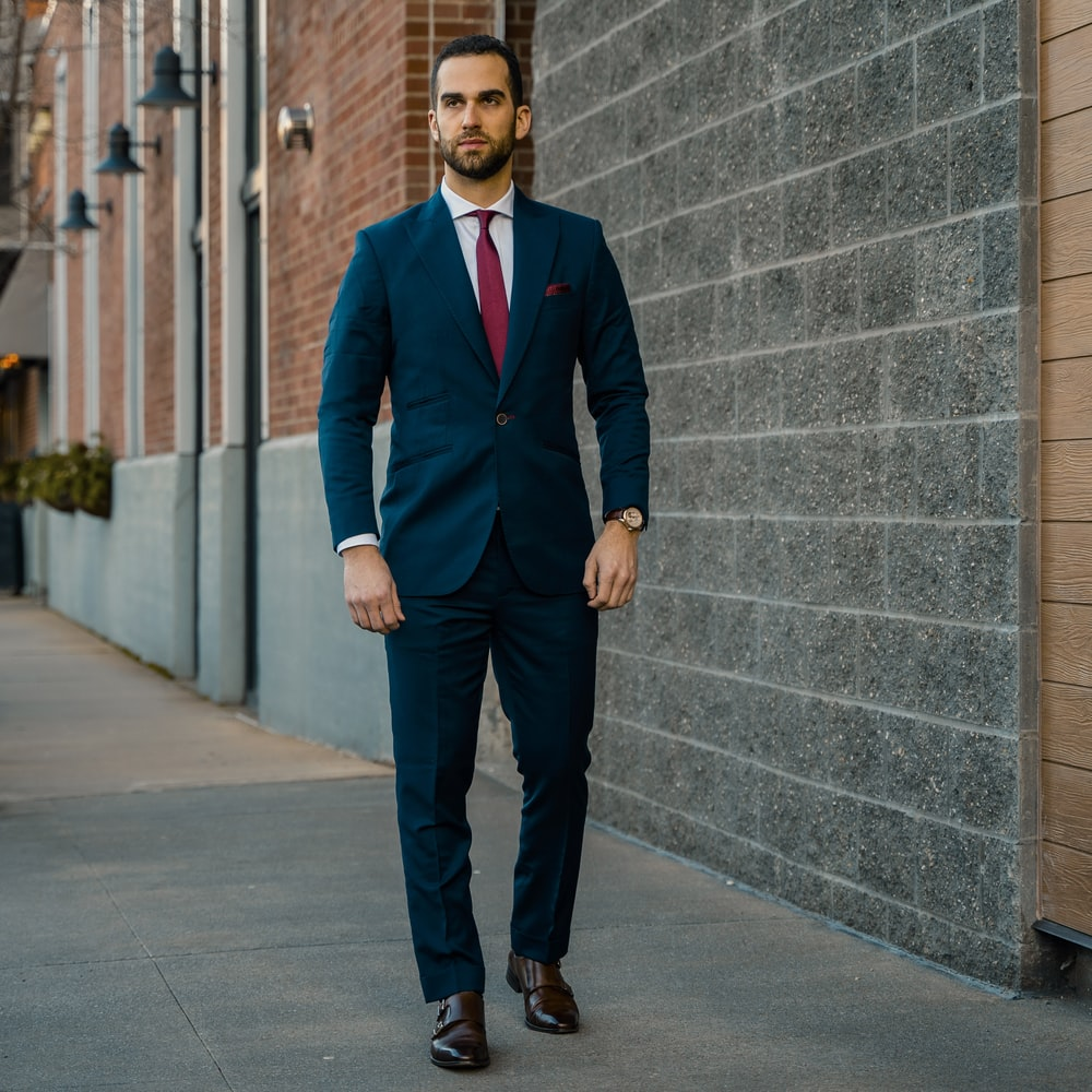 man in black suit standing beside gray concrete wall during daytime