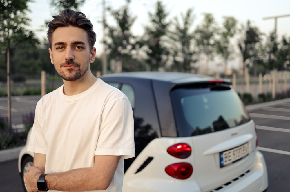 man in white crew neck t-shirt standing beside white car during daytime