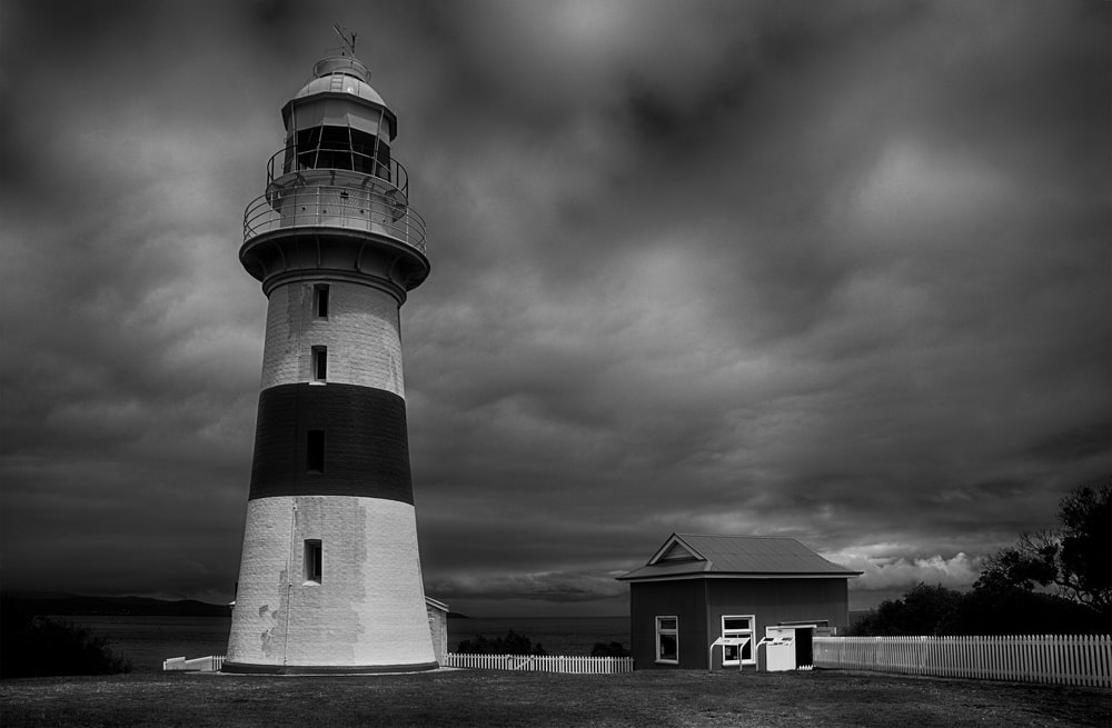 grayscale photo of lighthouse under cloudy sky