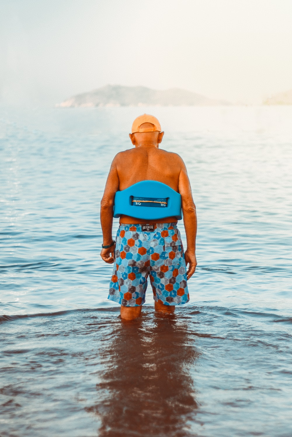 man in swimming trunks stood in sea