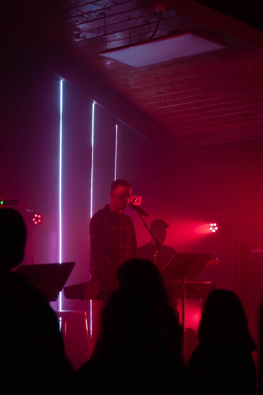 man in black suit singing on stage