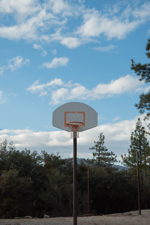 basketball hoop near trees under blue sky during daytime