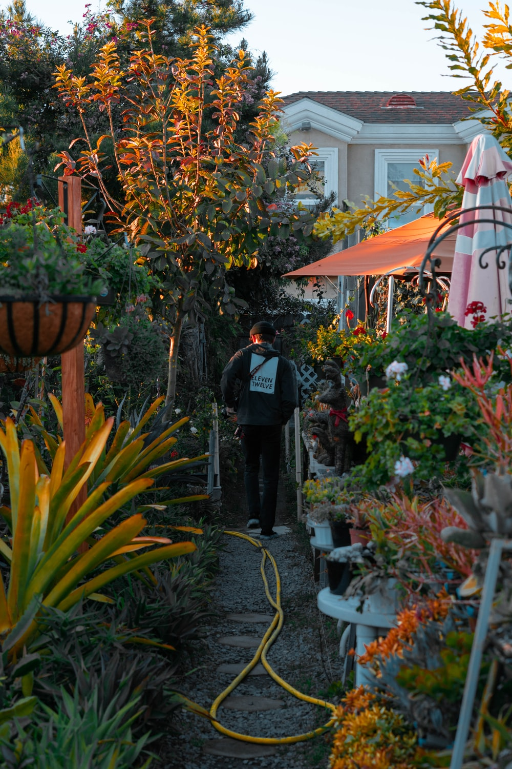 man in black jacket standing near green plants during daytime