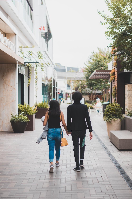 man and woman walking on sidewalk during daytime