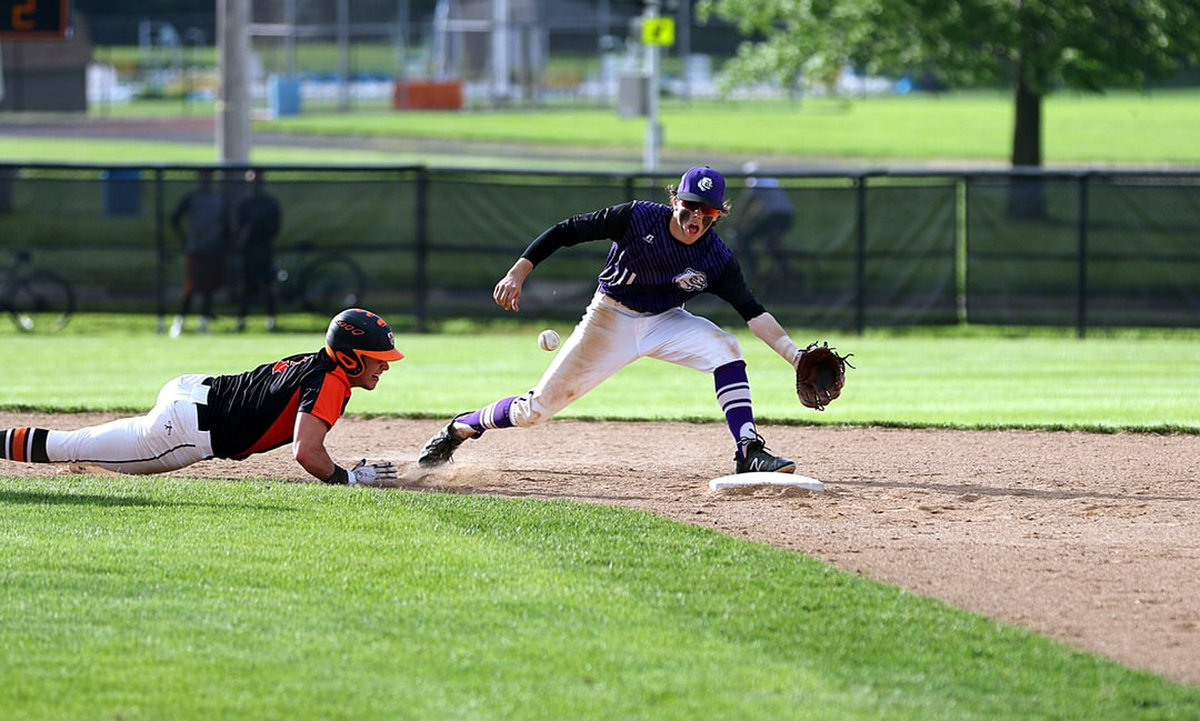 Baseball player diving to get back to second base.