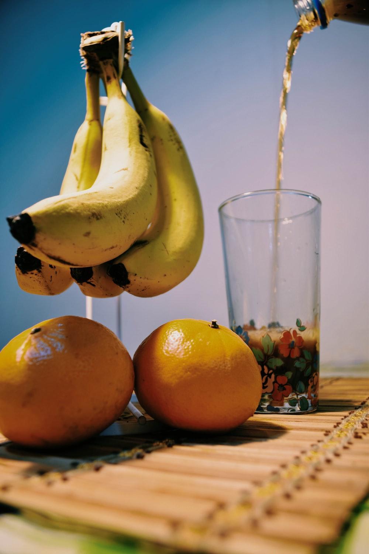 yellow banana fruit beside clear drinking glass