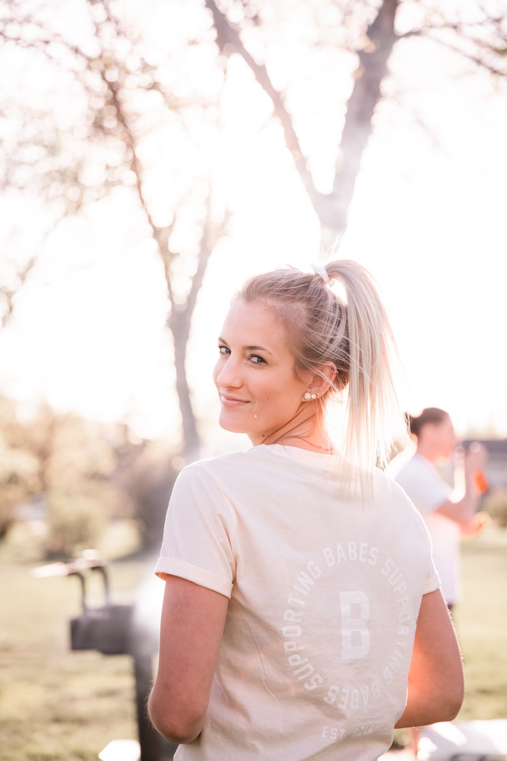 girl in white crew neck t-shirt standing near people during daytime