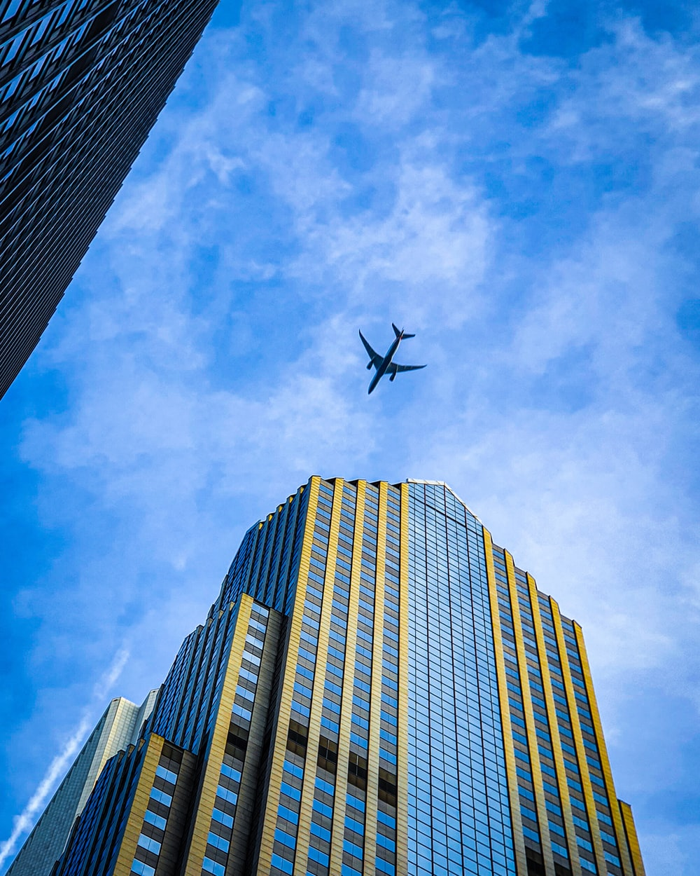 airplane flying over high rise building during daytime