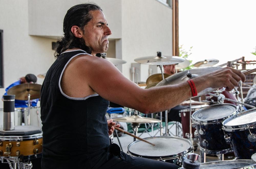 man in black tank top playing drum