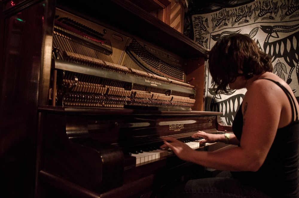 woman playing piano in grayscale photography