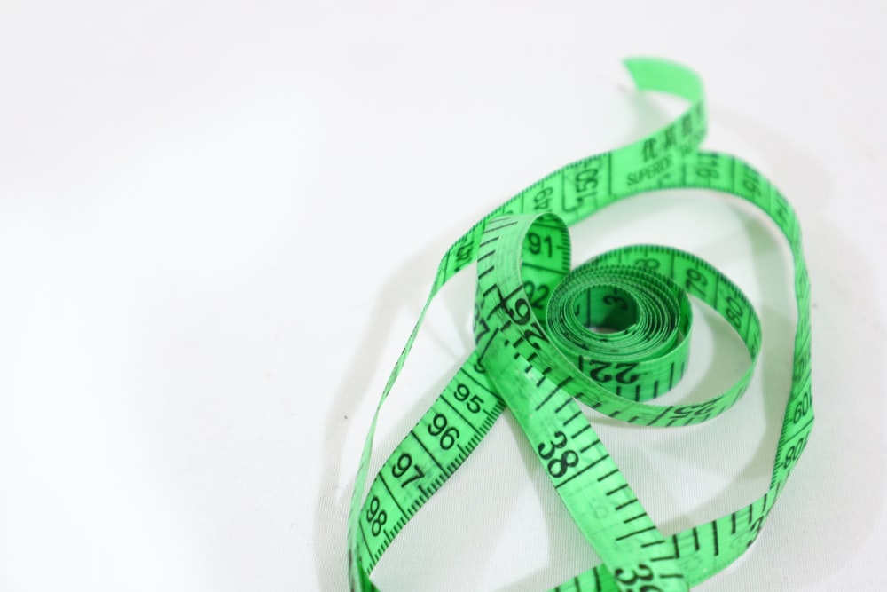 green and white ribbon on white surface